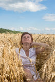 Young attractive girl in a wheat. Under the caressing sun. Stock Photos