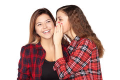 Young attractive girl whispering in the ear of his sister stock photos