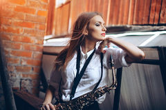 Young attractive girl in white shirt with a saxophone - outdoor in old town. young woman with sax thinking about something stock photos