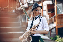 Young attractive girl in white shirt with a saxophone - outdoor in old town. young woman with sax thinking about something royalty free stock image
