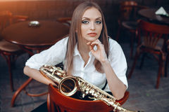 Young attractive girl in white shirt with a saxophone sitting on caffe shop - outdoor in street. young woman with sax looking royalty free stock image