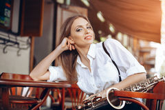 Young attractive girl in white shirt with a saxophone sitting on caffe shop - outdoor in street. young woman with sax looking royalty free stock photography