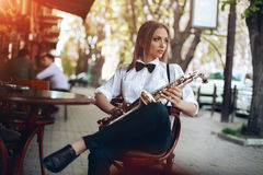 Young attractive girl in white shirt with a saxophone sitting near caffe shop - outdoor in sity. young woman with sax thinkin Stock Image