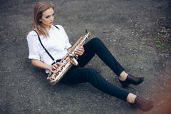 Young attractive girl in white shirt with a saxophone sitting sits on the earth - outdoor. young woman with sax thinking abou stock image