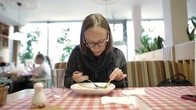 Young attractive girl or woman looking at smartphone while eating salad in cafe in the city. Unrecognizable people on. Young attractive girl or woman in stock video footage