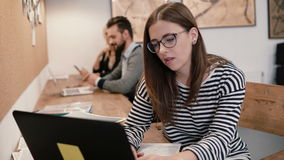 Young attractive girl working with laptop in a modern startup office. Young attractive brunette girl working with laptop in a modern startup office stock video footage