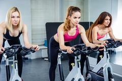 Young attractive girls do cardio training on a stationary bike at the gym. Young attractive girls do cardio training on a stationary bike at the gym Royalty Free Stock Images