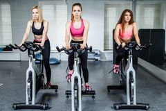Young attractive girls do cardio training on a stationary bike at the gym. Young attractive girls do cardio training on a stationary bike at the gym Stock Photography