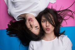 Young attractive girls making crazy faces. Young cute funny attractive girls making crazy faces isolated on pink and blue stock images