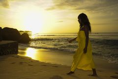 Glamorous African American black woman in chic and elegant summer dress posing relaxed walking on summer sunset beach Stock Photos