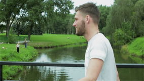 A young attractive guy with a beard is walking over a small bridge across the river. Smiling man goes on the bridge through the channel in the summer time. A stock video footage