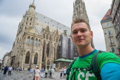 Young attractive guy with blue eyes taking selfie with huge church on background in europe stock photo