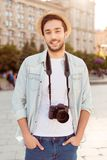 Young attractive guy is posing for photo of his summer holiday,. Outdoors in the town. He is in casual outfit, hat, with camera, hands are in the pockets of Royalty Free Stock Photos