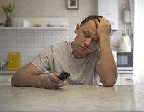 Young attractive guy with a TV remote is sitting in the kitchen royalty free stock photos