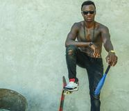 Young attractive and handsome black afro American man with fit muscular body and six pack holding baseball bat and skate board stock photo