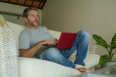 Young attractive and handsome happy man sitting at home sofa couch working with laptop computer netbook relaxed and cheerful in in Royalty Free Stock Images