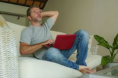 Young attractive and handsome happy man sitting at home sofa couch working with laptop computer netbook relaxed smiling cheerful i. Young attractive and handsome royalty free stock photos