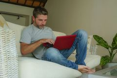 Young attractive and handsome happy man sitting at home sofa couch working with laptop computer netbook relaxed smiling thoughtful. Young attractive and handsome stock photo