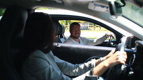 Young attractive handsome man driving car and talking with woman. Young attractive handsome man driving car and welcome woman in traffic on road stock footage