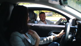 Young attractive handsome man driving car and talking with woman. Young attractive handsome man driving car and welcome woman in traffic on road stock video footage