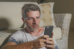 Young attractive and handsome man sitting at living room floor focused and concentrated using mobile phone networking or dating. Online relaxed in internet work stock image