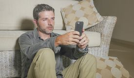 Young attractive and handsome man sitting at living room floor focused and concentrated using mobile phone networking or dating. Online relaxed in internet work royalty free stock image