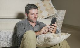 Young attractive and handsome man sitting at living room floor focused and concentrated using mobile phone networking or dating. Online relaxed in internet work royalty free stock images