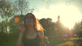 Young attractive handsome pretty adult girl playing with soap bubbles, outdoor having fun stock footage