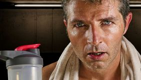 Young attractive and handsome sport man at fitness club sweating after workout hard training looking defiant with towel on his stock image