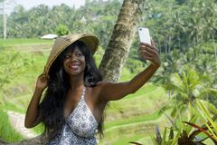 Young attractive happy afro american black woman tourist taking selfie portrait photo with mobile phone camera. While exploring rice fields forest and jungle in stock images