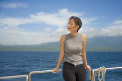 Young attractive and happy Asian Chinese woman on excursion ship or ferry  enjoying sea breeze on summer holiday sea boat trip Royalty Free Stock Photography