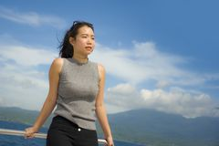 Young attractive and happy Asian Chinese woman on excursion ship or ferry  enjoying sea breeze on summer holiday sea boat trip Royalty Free Stock Images
