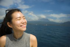 Attractive and happy Asian Chinese woman on excursion ship or ferry looking ocean and island enjoying sea breeze on summer holiday. Young attractive and happy Stock Images
