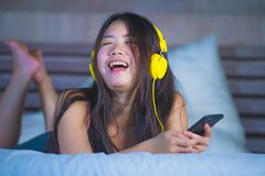 Young attractive and happy Asian Chinese woman with yellow headphones listening to music in mobile phone on bed at home smiling ha. Ving fun with internet song royalty free stock images