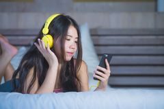 Young attractive and happy Asian Chinese woman with yellow headphones listening to music in mobile phone on bed at home smiling ha. Ving fun with internet song stock photo