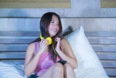 Young attractive and happy Asian Chinese woman with yellow headphones listening to music in mobile phone on bed at home smiling ha. Ving fun with internet song royalty free stock photography