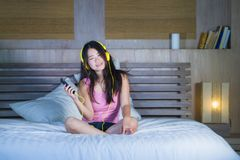 Young attractive and happy Asian Chinese woman with yellow headphones listening to music in mobile phone on bed at home smiling ha. Ving fun with internet song royalty free stock photos