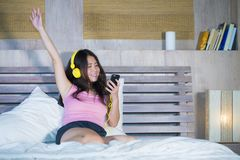Young attractive and happy Asian Chinese woman with yellow headphones listening to music in mobile phone on bed at home smiling ha. Ving fun with internet song stock image