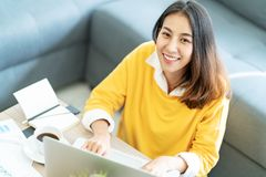 Young attractive happy asian female student sitting at living room floor smiling and looking up at camera royalty free stock image