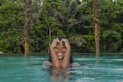 Young attractive happy black African American woman enjoying holidays in tropical resort infinity pool to beautiful jungle landsca. Young attractive and happy Royalty Free Stock Photos