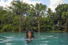 Young attractive happy black African American woman enjoying holidays in tropical resort infinity pool to beautiful jungle landsca. Young attractive and happy Stock Photography