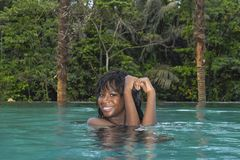 Young attractive happy black African American woman enjoying holidays in tropical resort infinity pool to beautiful jungle landsca. Young attractive and happy Stock Photos