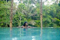 Young attractive happy black African American woman enjoying holidays in tropical resort infinity pool to beautiful jungle landsca. Young attractive and happy Stock Image