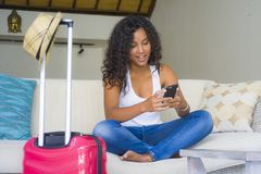 Young attractive and happy black African American woman at home with suitcase using mobile phone leaving for holidays trip in tour royalty free stock photos