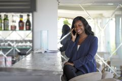 Attractive and happy black african american woman working from restaurant bar talking on mobile phone stock photo