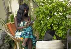 Happy black afro american woman in elegant dress working on luxury terrace villa with laptop and mobile phone Royalty Free Stock Photos