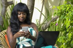 Happy black afro american woman in elegant dress working on luxury terrace villa with laptop and mobile phone. Young attractive and happy black afro american stock photos