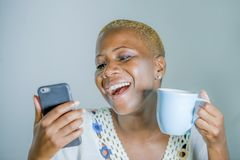 Young attractive and happy black afro American woman ho. Lding tea or coffee cup using internet social media app on mobile phone smiling cheerful and excited in royalty free stock images