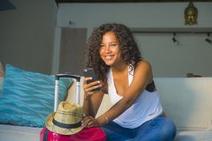 Young attractive and happy black afro American woman at home with suitcase using mobile phone leaving for holidays trip in tourism royalty free stock photography