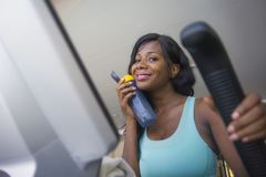 Young attractive and happy black afro American woman training elliptical machine workout at fitness club smiling cheerful drinking stock image